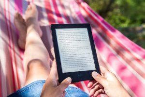 Eine Person liest ein E-Book in der Hängematte