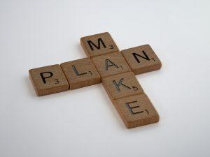 Mit Scrabble-Steinen gelegte Wörter: vertikal MAKE, horizontal PLAN; beide Wörter kreuzen sich beim A, sodass der Satz MAKE A PLAN entsteht.